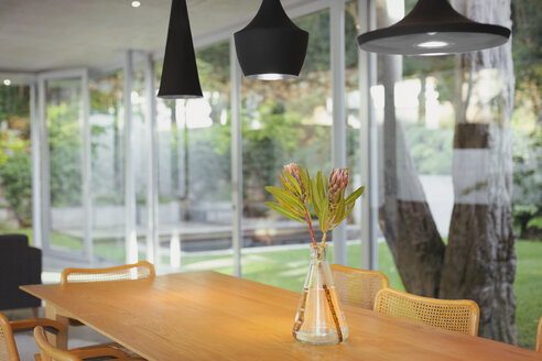 Modern black pendant lights hanging over bouquet on dining room table - HOXF02035
