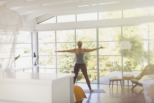 Woman practicing yoga with arms outstretched in sunny modern bedroom - HOXF02056
