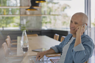 Smiling mature man talking on cell phone at dining table - HOXF02059