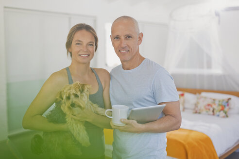 Portrait smiling mature couple with dog and digital tablet in bedroom - HOXF02062