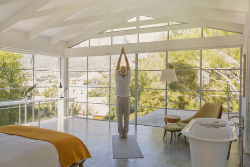 Mature man practicing yoga with hands clasped overhead in luxury bedroom - HOXF02065