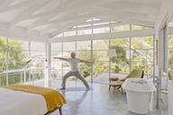 Mature man practicing yoga warrior 2 pose in luxury bedroom - HOXF02068