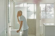 Mature man touching face at bathroom mirror - HOXF02074