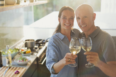 Portrait happy mature couple toasting white wine glasses, cooking in kitchen - HOXF02089