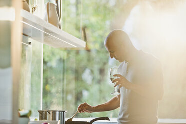 Mature man drinking white wine and cooking at stove in sunny kitchen - HOXF02095