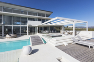 Sunny modern luxury home showcase exterior with lounge chairs and swimming pool - HOXF02107
