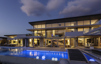 Illuminated modern luxury home showcase exterior with swimming pool at night - HOXF02110