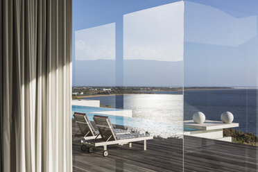 Window view of sunny modern luxury patio with infinity pool and ocean view - HOXF02137