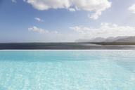 Sunny, tranquil infinity pool with ocean view under blue sky with clouds - HOXF02143