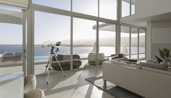 Sunny, tranquil modern luxury home showcase interior living room with telescope and ocean view - HOXF02146