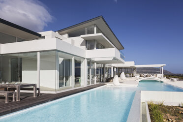 Sunny, tranquil modern luxury home showcase exterior with swimming pool - HOXF02149