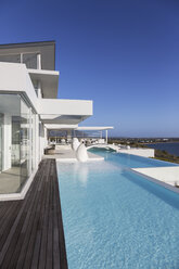 Sunny, tranquil modern luxury home showcase exterior with infinity pool - HOXF02152