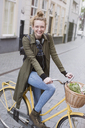 Portrait smiling young woman with headphones riding bicycle with produce in basket - HOXF02206