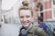 Portrait smiling young woman with headphones on city street - HOXF02215