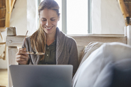 Smiling woman with eyeglasses using laptop on sofa - HOXF02233