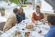 Couples drinking white wine and and eating lunch at patio table - HOXF02236