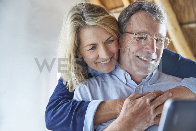 Affectionate couple hugging and using laptop - HOXF02239 - Ryan Lees/Westend61