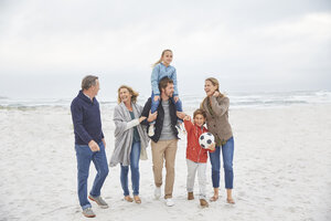 Multi-generation family walking on winter beach - HOXF02257
