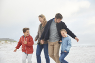 Playful family on winter beach - HOXF02269