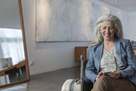 Smiling mature woman with suitcase texting with cell phone - HOXF02332