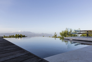 Tranquil luxury infinity pool with mountain view below blue sky - HOXF02371