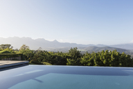 Tranquil luxury infinity pool with mountain view below sunny blue sky - HOXF02389