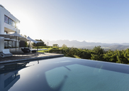 Tranquil, sunny home showcase exterior with infinity pool and mountain view under blue sky - HOXF02395