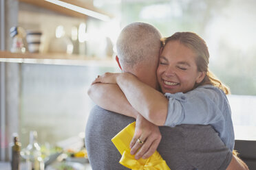 Happy couple hugging in kitchen - HOXF02422