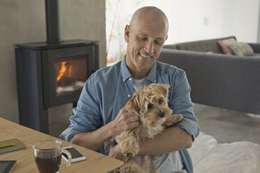 Smiling man petting dog in front of wood stove fireplace - HOXF02431