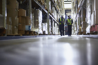 Workers walking in distribution warehouse aisle - HOXF02440