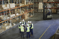 Workers meeting in a circle in distribution warehouse - HOXF02443