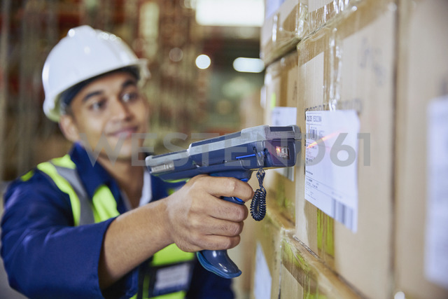 Worker with scanner scanning barcode on box in distribution warehouse - HOXF02446