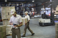 Workers carrying and moving boxes with forklift at distribution warehouse loading dock - HOXF02449