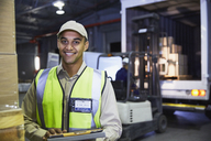 Portrait smiling worker in front of forklift and truck at distribution warehouse loading dock - HOXF02461
