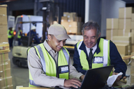 Manager and worker using laptop at distribution warehouse loading dock - HOXF02464