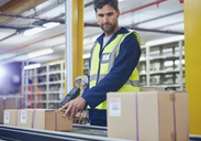 Worker scanning and processing boxes on conveyor belt in distribution warehouse - HOXF02470