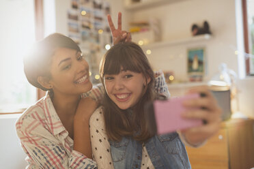 Playful young women taking selfie with camera phone - HOXF02488