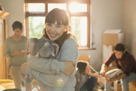 Portrait smiling young woman hugging stuffed elephant - HOXF02530