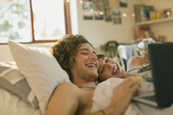 Smiling young couple laying in bed using laptop - HOXF02539