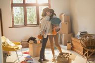 Mother and daughter hugging unpacking boxes in apartment - HOXF02542