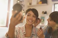 Young women friends applying makeup - HOXF02587