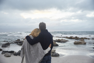 Serene affectionate couple hugging on winter beach looking at ocean - HOXF02605
