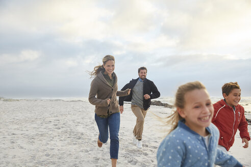 Playful family running on beach - HOXF02608
