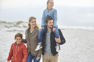Family walking on winter beach - HOXF02623