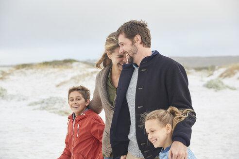 Happy family walking on winter beach - HOXF02638