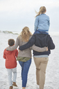 Family walking on winter beach - HOXF02647
