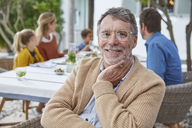Portrait smiling senior man enjoying patio lunch with family - HOXF02656