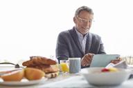 Senior man using digital tablet at patio breakfast - HOXF02659