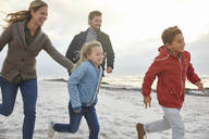 Playful family running on winter beach - HOXF02677