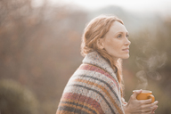 Serene woman wrapped in blanket drinking hot coffee outdoors - HOXF02680